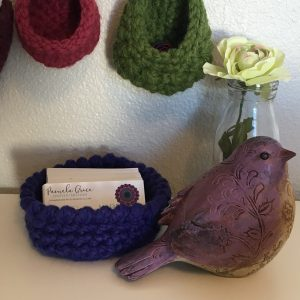 Photo of a blue Free Universal Bowl Crochet Pattern with small hanging baskets