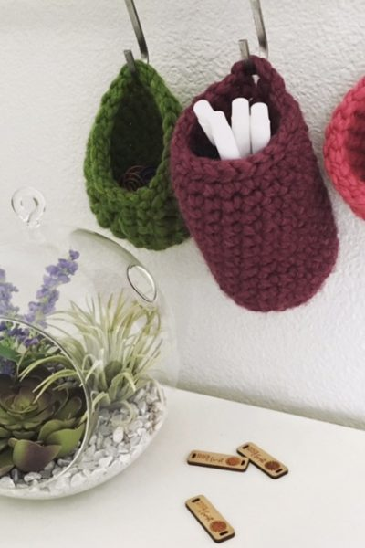 three small crocheted hanging baskets, hung on S hooks with a glass terrarium on the desk