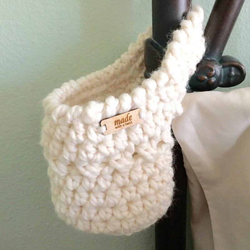 Photo of a cream colored crocheted basket with a handle, hanging from a bed post. The basket has a wooden tag attached that says Made with a Twist.