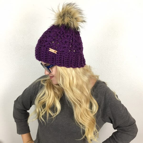 A photo of a blonde woman wearing the McKenna Pompom Beanie