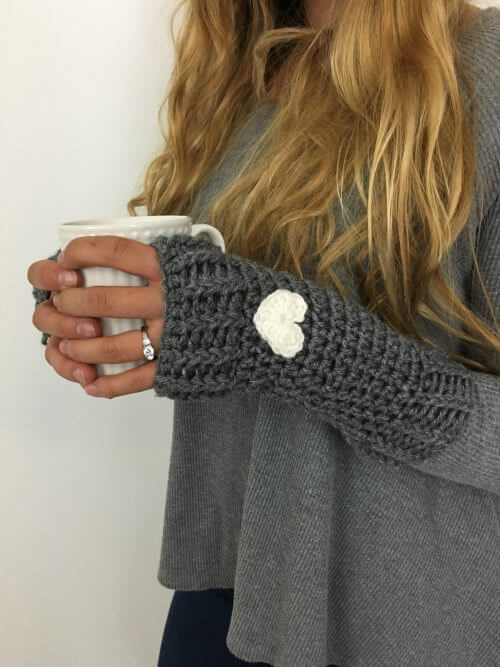 A photo of a woman wearing a gray Loveland Fingerless Gloves FREE Crochet Pattern