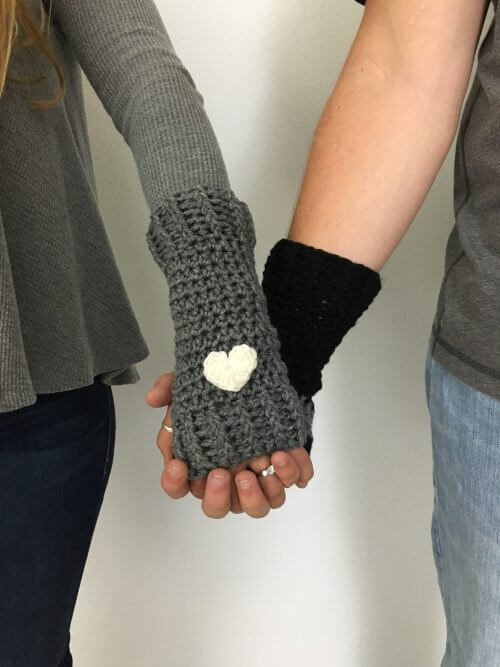 Photo of 2 holding hands while wearing a gray and black crocheted Loveland Fingerless Gloves