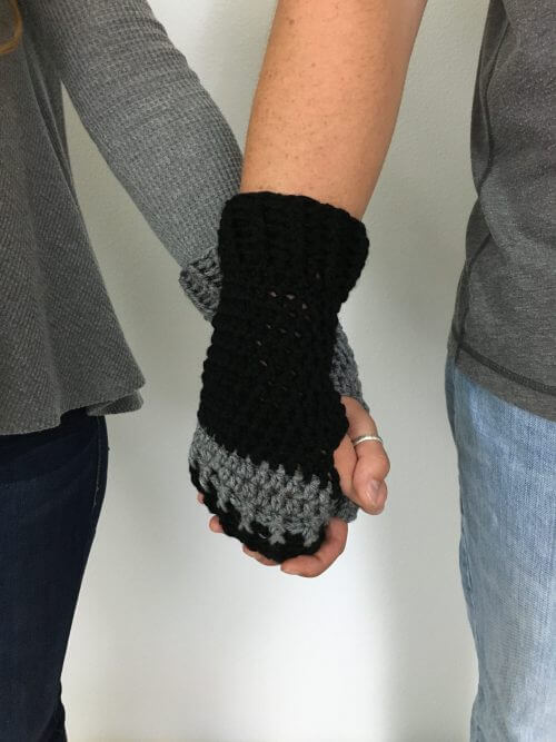 Photo of 2 holding hands while wearing a gray and black Loveland Fingerless Gloves FREE Crochet Pattern