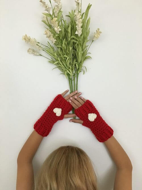 Photo of a woman wearing the Loveland Fingerless Gloves while holding a bunch of flowers