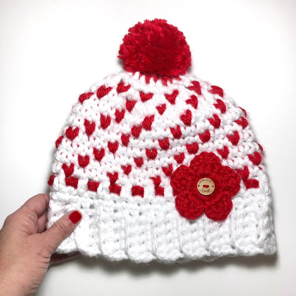 A close up image of the white and red crocheted Heartful Winter Hat with white background