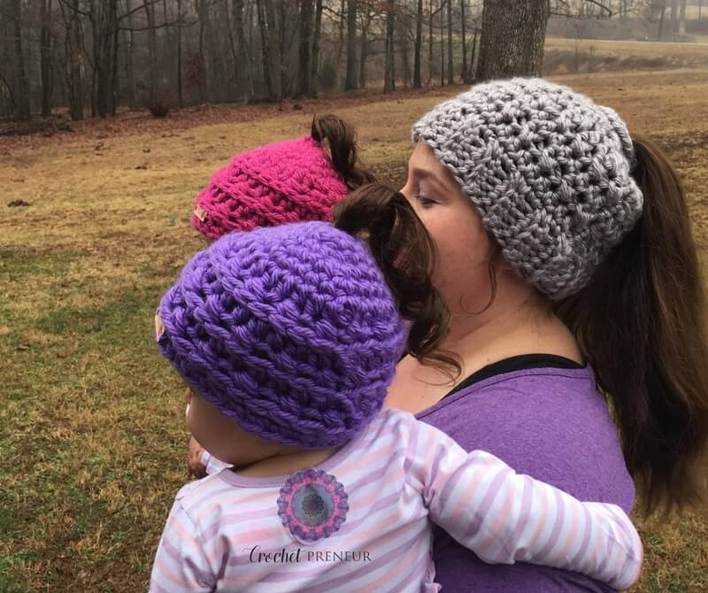 Photo of a mother carrying 2 little girls wearing the crocheted Phoneytail Hat side view