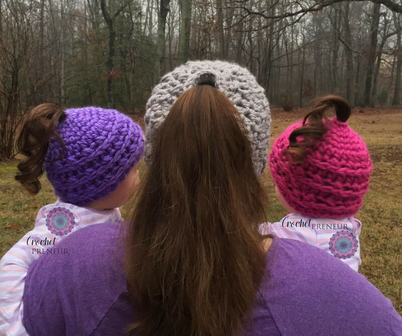 Photo of a mother carrying 2 little girls wearing the crocheted Phoneytail Hat back view
