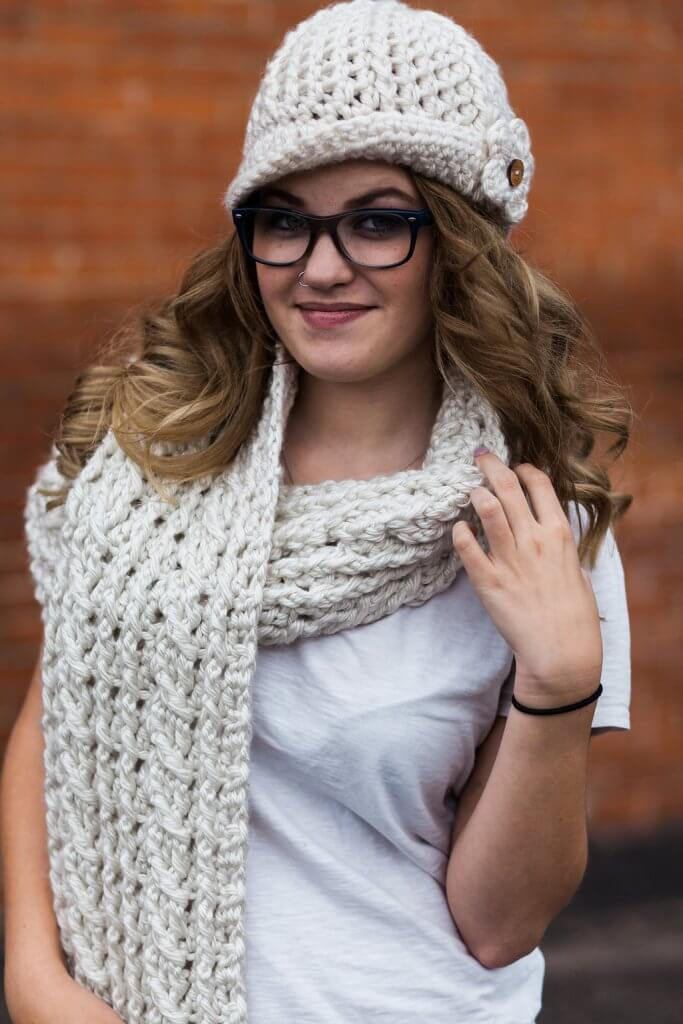 A woman wearing the Ardara Oversized Cable Scarf with a crocheted hat