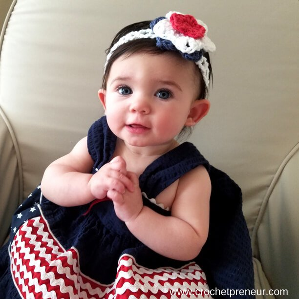 An image of a baby wearing the Stars & Stripes Summer Headband FREE Crochet Pattern