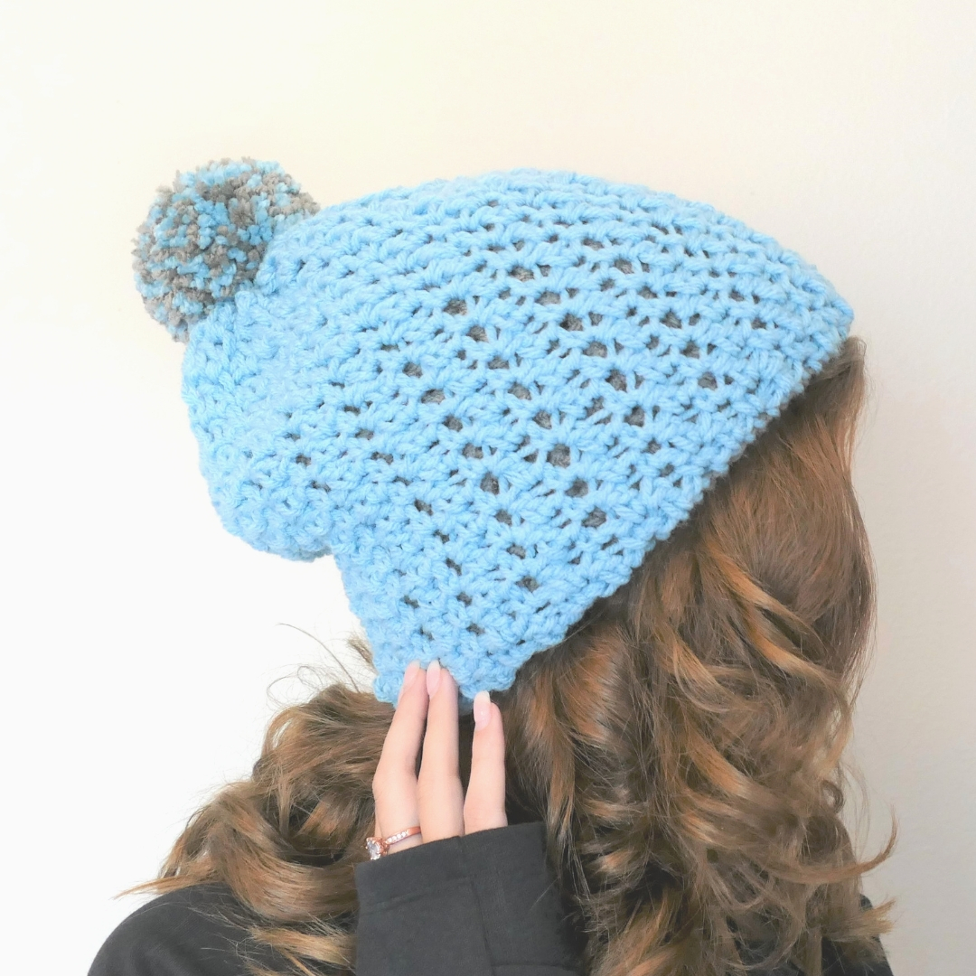 polly double thick reversible crochet hat in aqua blue with a grey pompom worn by a blond haired girl
