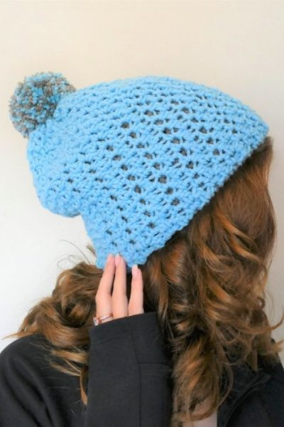 square photo of woman wearing an aqua colored hat with an aqua and grey pompom