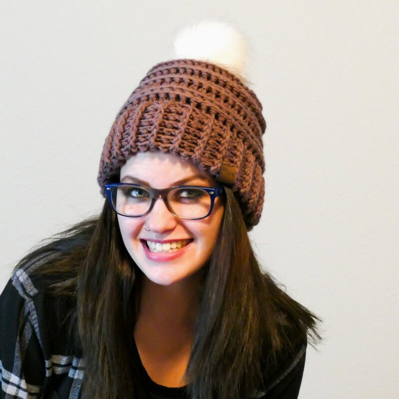 A woman wearing the crocheted Keystone Ribbed Hat with white background