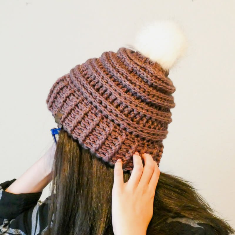 Photo of a woman showing the back of the crocheted Keystone Ribbed Hat