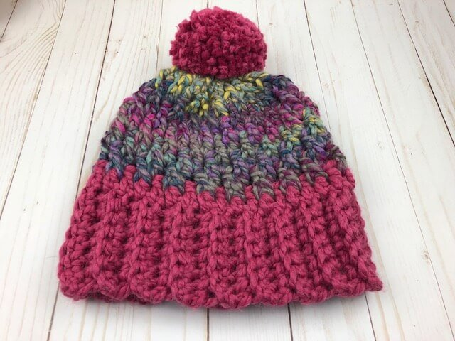 A photo of a crocheted unisex winter hat with a wooden background