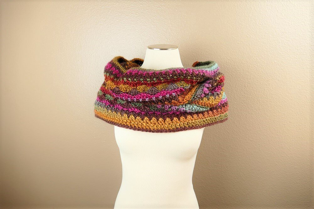 A photo of a hooded crochet multicolored cowl that can be worn as a head wrap or neck warmer..