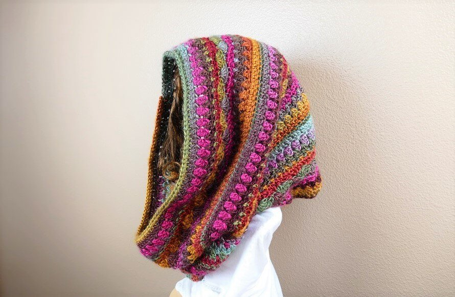 Photo of a side view woman wearing the crocheted Sweet Harmony Hooded Cowl