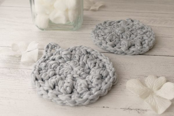 Closeup photo of two grey crocheted facial scrubbies on a white wooden backdrop