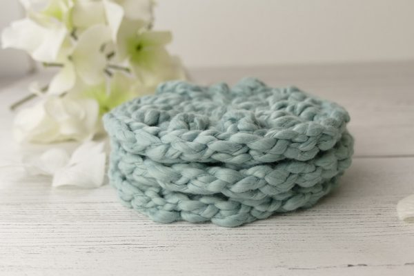 3 crocheted facial scrubbies stacked on top of one another
