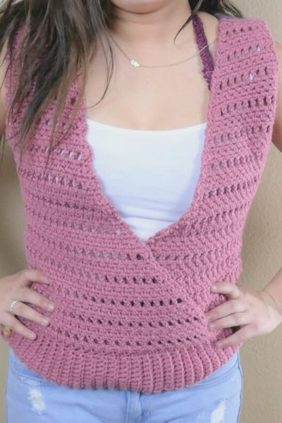Photo of a teenage girl's torso. She's wearing a pink crocheted top with a v-neck and criss crossing panels. She has brown hair, a white tank top, jeans and her hands on her hips.