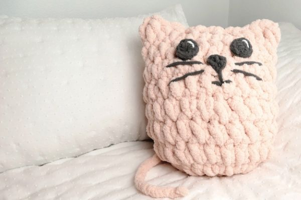 Image of a crochet pink cat pillow resting on a bed with white linens