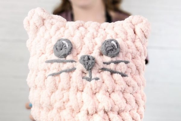 A close-up image of a pink crochet cat pillow