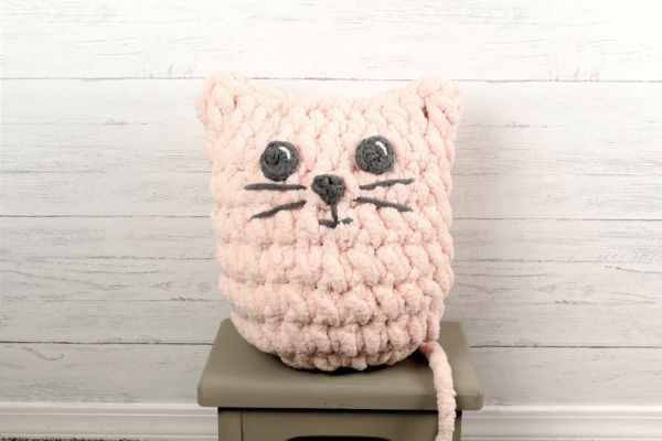 A crocheted pink cat pillow sitting on a grey footstool with a white wooden slat wall