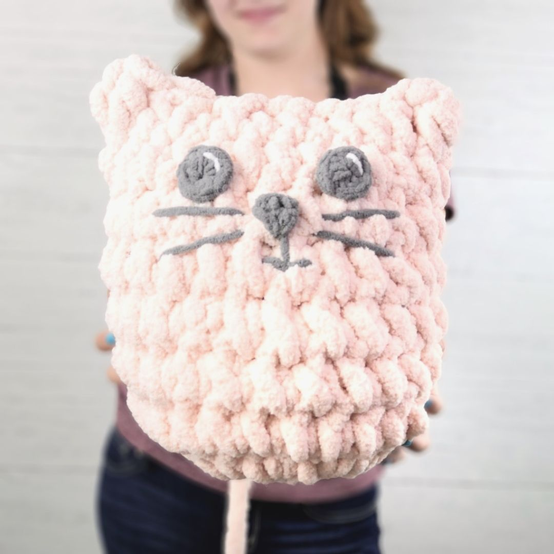 square photo of a young woman hold a jumbo cat pillow close to the camera. The woman is blurred int he background