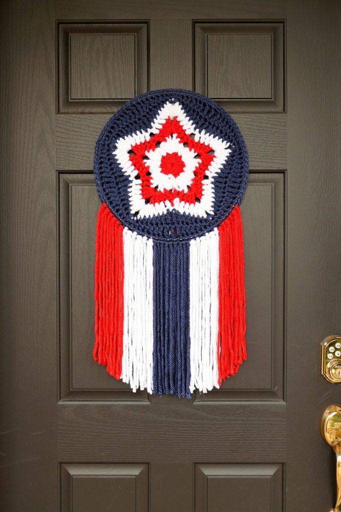 A red, white, and blue granny star mandala hanging on a black door to celebrate the 4th of July