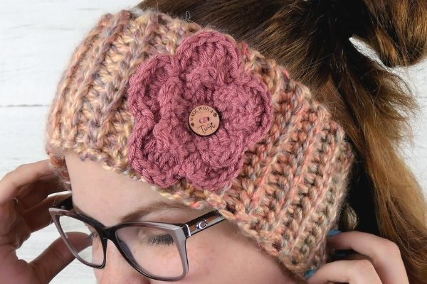 Close up image of the flower on the everly headband cowl. In the center of the flower is a button that reads made with a twist.