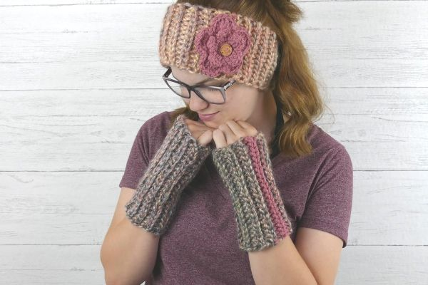 A photo of a young woman with glasses wearing a handmade headband with a floral embellishment. Her hands are near her face and she is wearing easy ribbed fingerless gloves