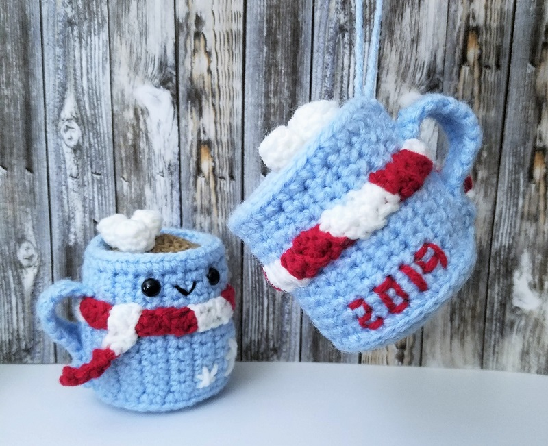 Photo showing the back of the blue hot chocolate amigurumi with another one on a table