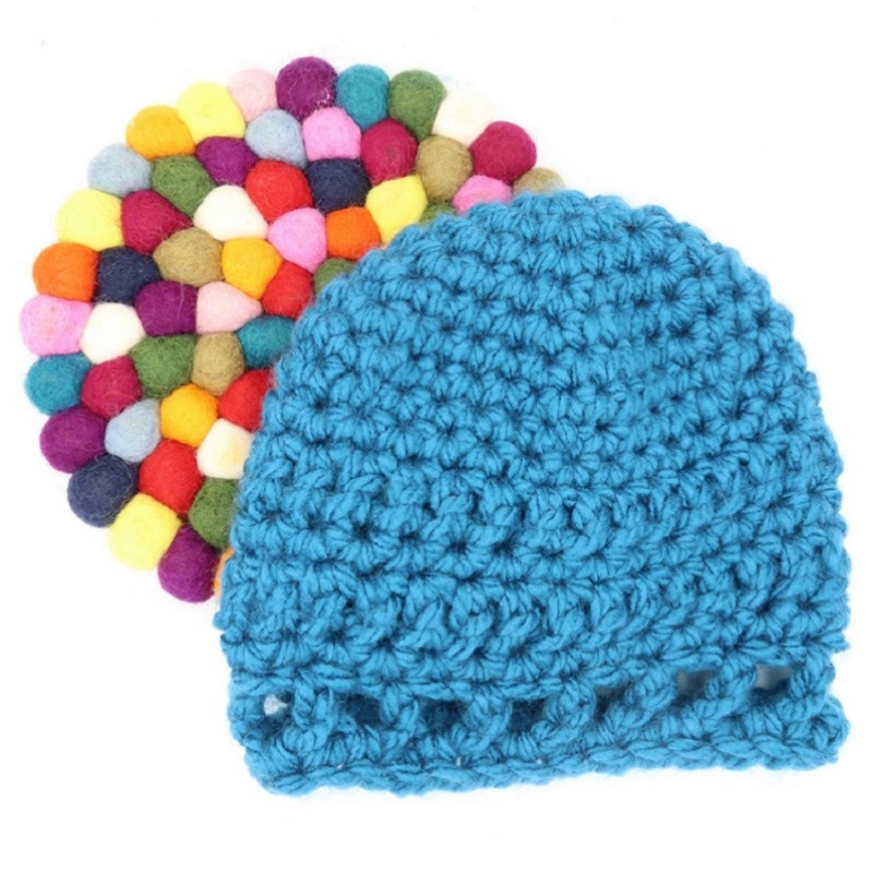 Photo of the blue Peek-a-boo Baby Hat with a colorful coaster at the back