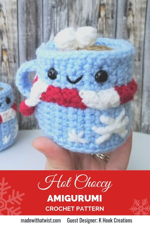 Picture of blue hot chocolate amigurumi wearing a red and white scarf