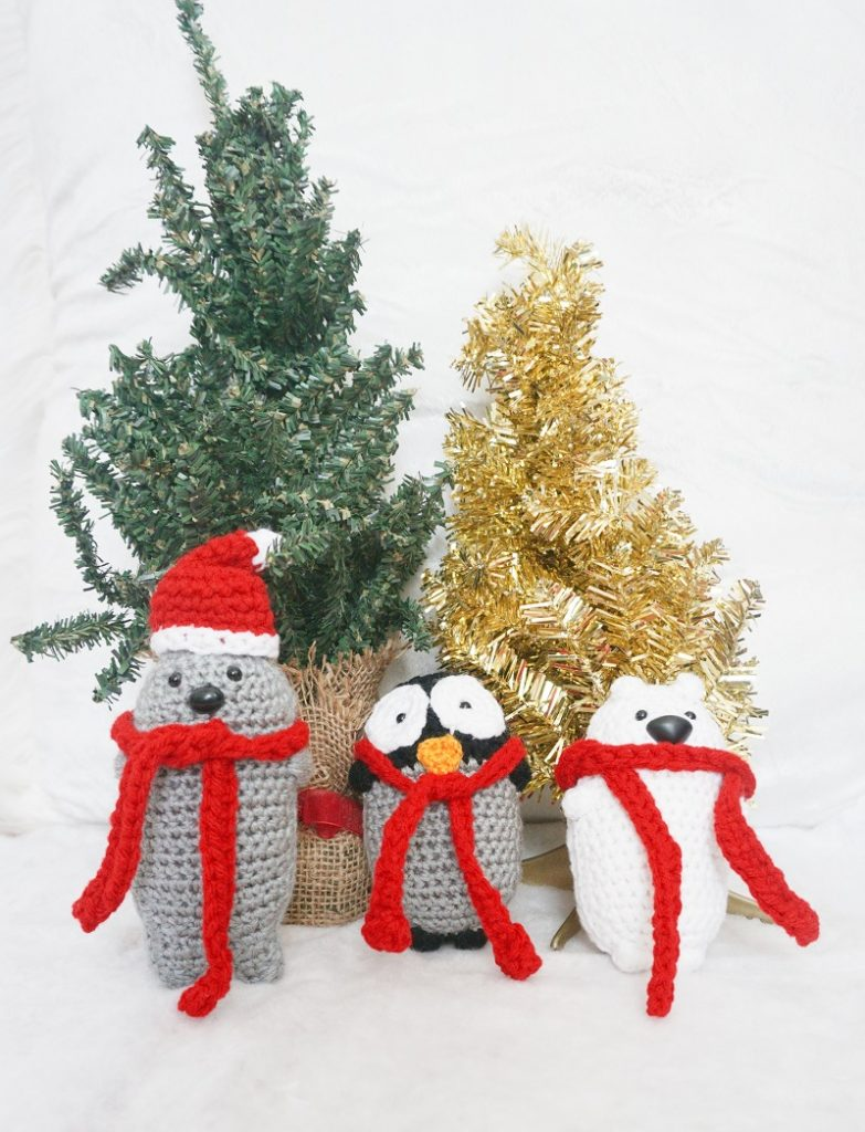 Photo of Amigurumi crochet seal, penguin, and polar bear in front of Christmas ornaments