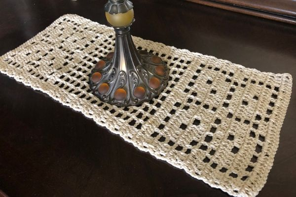 Image of free crochet table runner pattern, Autumn Leaves, placed on a dark dresser with an antique lamp on top.