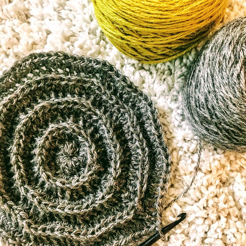 Close up photo of the unfinished hat with hook and yarns