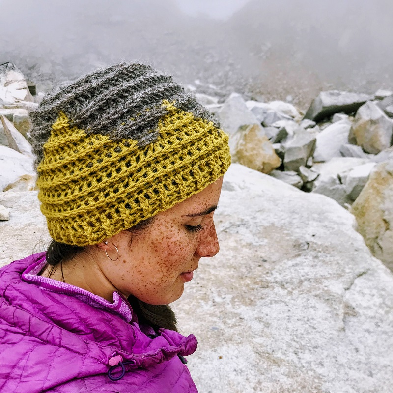 Photo of a woman wearing the FREE crochet beanie pattern while she is in the rocky outdoors
