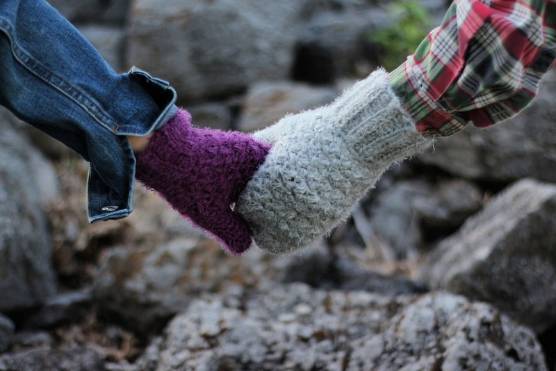 2 people holding hands wearing crochet hygge mittens