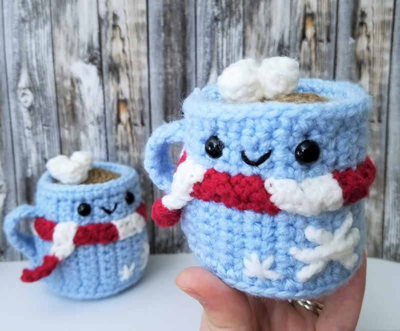 A hand holding the blue hot chocolate amigurumi wearing red and white scarf closer
