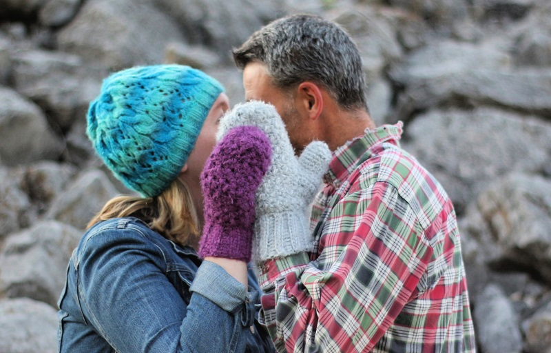 Photo of a man and woman wearing crochet hygge mittens.