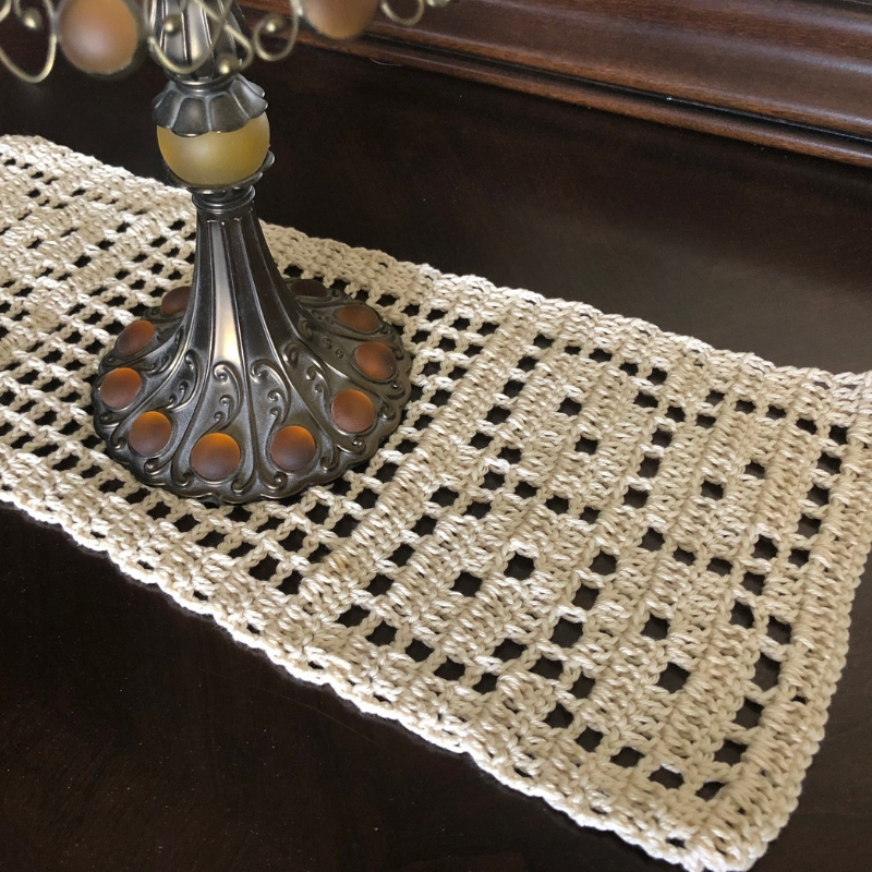 square image of autumn leaves table runner on a dark dresser with an antique lamp on top
