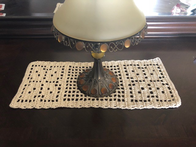 Autumn leaves table runner, horizontal, with an antique lamp on top.