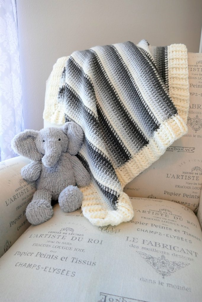 Photo of the crocheted Tunisian Baby Blanket draped on top of a sofa with an elephant stuffed toy