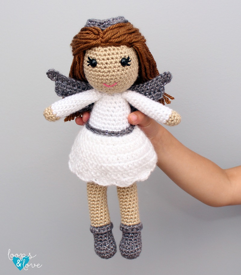 Photo of a hand holding the crocheted amigurumi angel