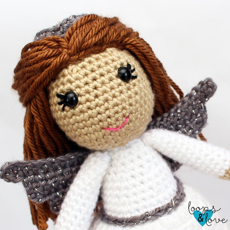 Close up image of the crocheted amigurumi angel's face