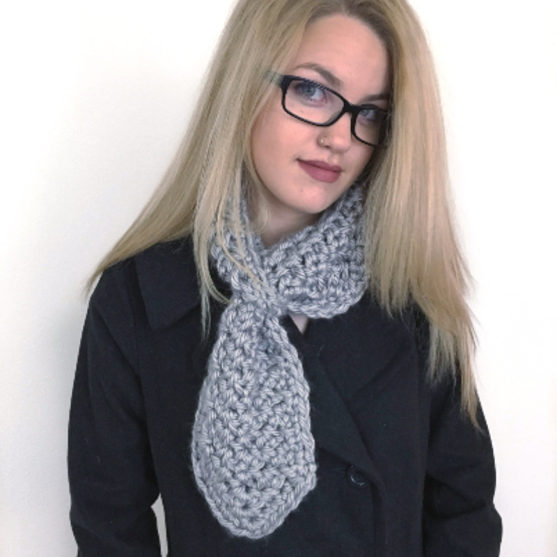 Photo of a blonde wearing glasses, a black coat, and a soft chunky neck warmer