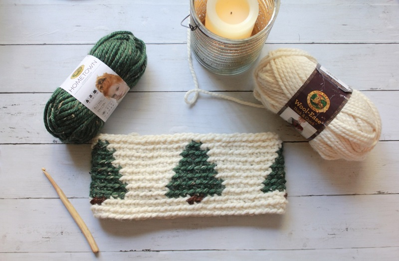 Image of the crocheted pinewood cowl on a wooden table with wooden hook, 2 colored yarns, and a candle on a tin can