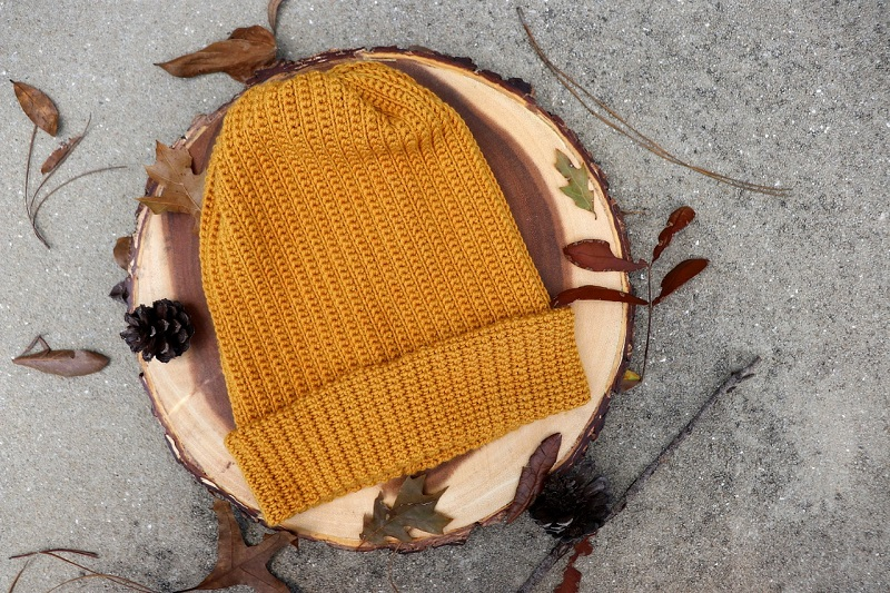 Photo of a beanie on top of a circle plank of wood with pine cones and dried leaves