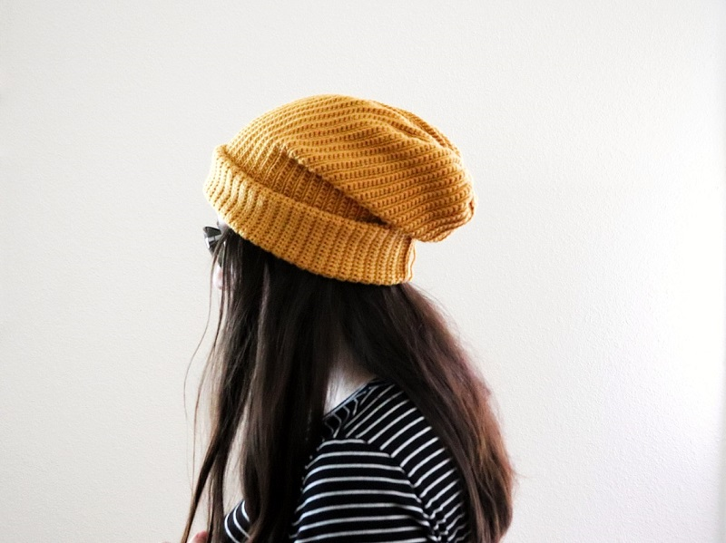 Photo of a person wearing stripped shirt and the crocheted slouchy beanie while the woman is looking away from the camera
