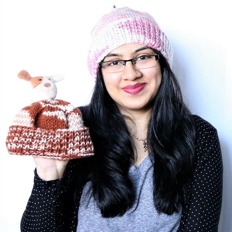 Photo of guest designer Noorain Nizami wearing a beanie and holding a cute hat version for kids